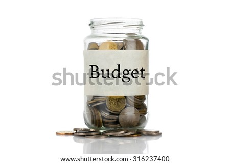 """Budget"" text label on full coins of jar spill out from it isolated on white background - saving, donation, financial, future investment and insurance concept - stock photo"