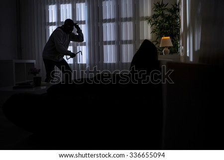 burglary with crowbar breaking into a home at night - stock photo