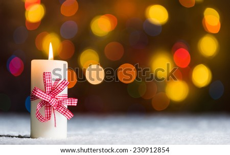 Burning candle with red bow, in snow, with defocussed fairy lights, bokeh in the background, Festive Christmas background with copyspace