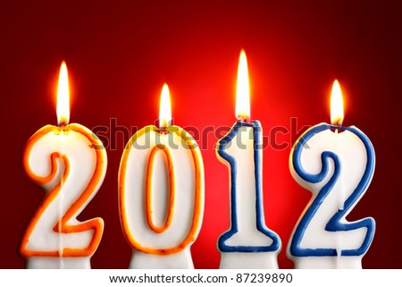 2012 burning candles close-up over red background - stock photo