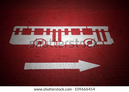 Bus and traffic direction sign painted on red asphalt road - stock photo