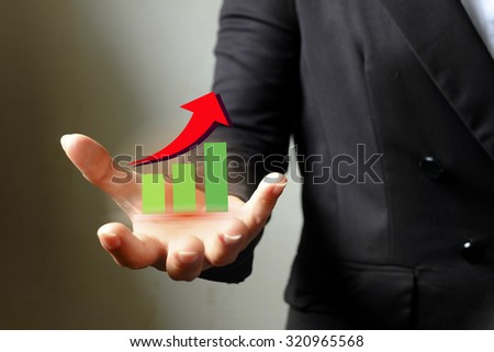 business growth Hand holding a rising arrow on mobile , business idea concept - stock photo