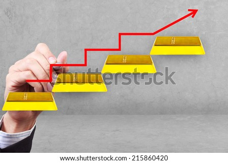 business hand and graph with rising arrow gold bars idea success business on transparent glass idea concept for success and growth - stock photo