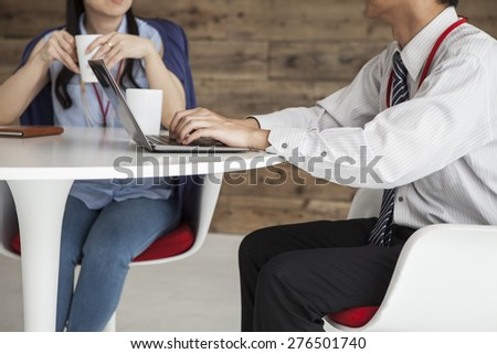 Business man and woman working on a laptop while having a meeting. - stock photo