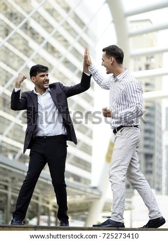 business man  from middle east talking and hand shake or hi five  to Caucasian white business man outdoor.