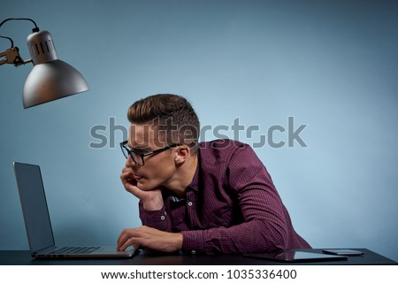 business man sitting at table looking at laptop, office