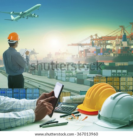 business man using computer tablet on working table in container dock  with transportation background - stock photo