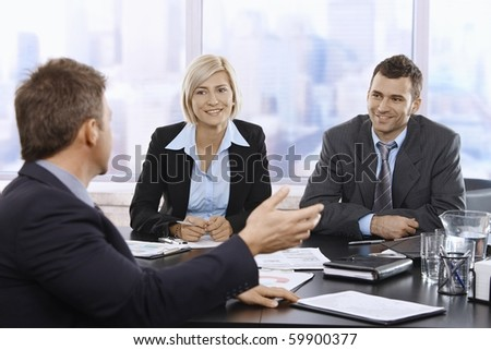 Business meeting in skyscraper office with smiling mid-adult professionals.?