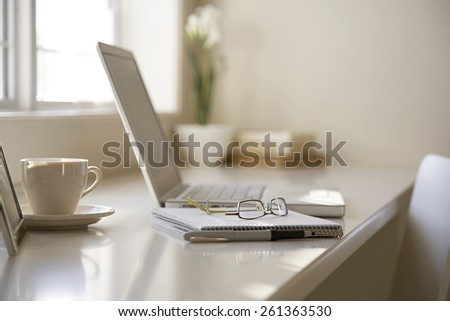 business table with a cup of coffee and laptop - stock photo