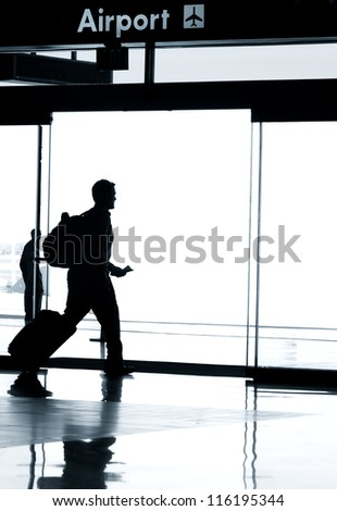 Business travel photo concept - Silhouette of business man walking in airport with luggage - stock photo
