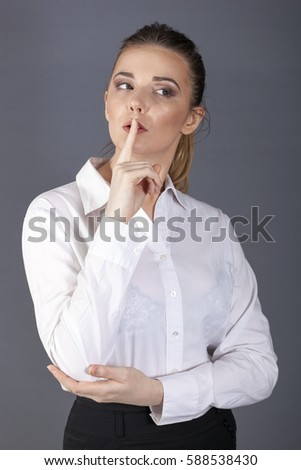 business woman or secretary  holds  finger at  mouth, silence symbol. Look aside