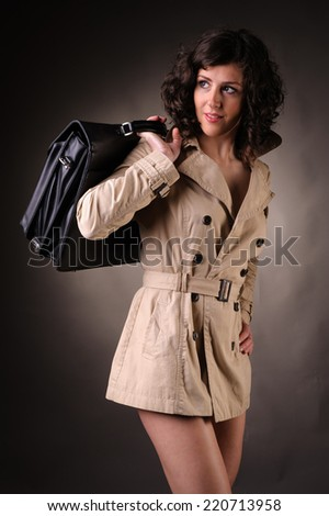 business woman wearing a raincoat and suitcase - stock photo