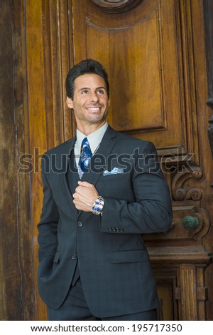 Businessman. Dressing in a dark blue suit, patterned necktie, holding a fist, a handsome, sexy, middle age businessman is standing by an old fashion style office door, confidently looking up. - stock photo