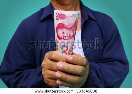 Businessman hand grabbing money, China money (RMB) bills - stock photo