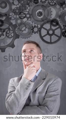 businessman looking at mechanism of cogwheels - stock photo