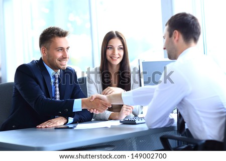 businessman shaking hands to seal a deal with his partner - stock photo