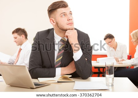Businessman sitting at the table  working with laptop