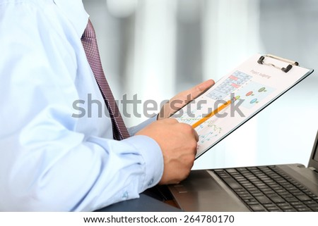 businessman sitting in front of laptop,  analyzing  data in  graphs in the office - stock photo