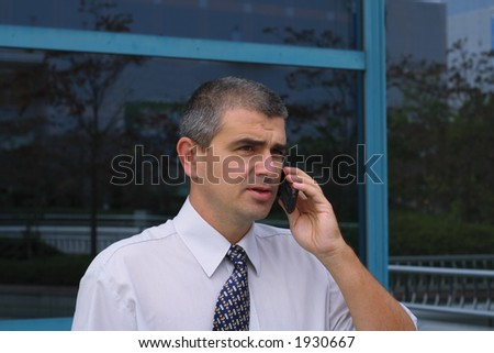 Businessman using a mobile phone in front of a corporate building - stock photo