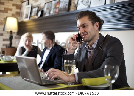 Businessman using laptop in cafe