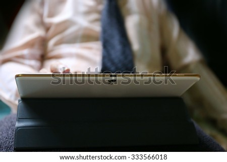 businessman with necktie hand use tablet working, Asian man holding a digital tablet, hands of a man holding blank tablet device over a wooden work space table, internet