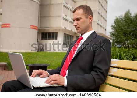 Businessman with notebook sits on the bench at the city park