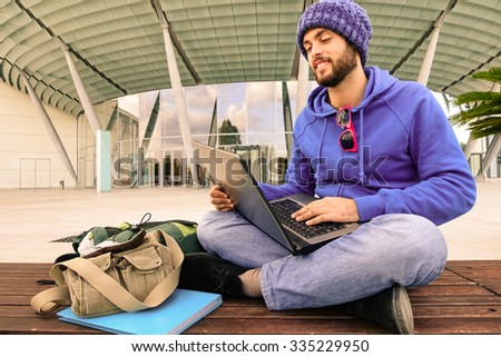 Businessman with pc sitting outdoor - Attractive guy smiling using laptop online - Trendy hipster working with computer on line outside modern building - Internet technology concept and lifestyle - stock photo