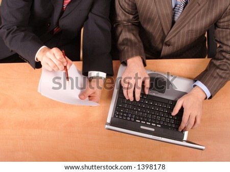 2 businessmen with laptop and blank paper sitting at the desk - no heads included...