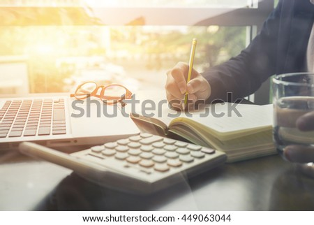 Businessperson Signing Contract,Form,writing paper at the desk with pen and reading books at table,in office,going to sign an agreement,divorce papers,morning light ,selective focus.  - stock photo