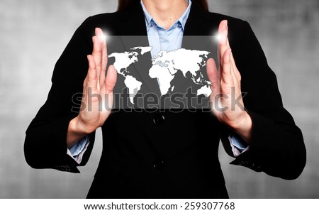 Businesswoman in dark suit holds world map global communication - stock photo