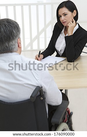Businesswoman interviewing disabled job candidate in his office  - stock photo