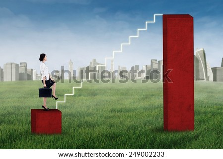 Businesswoman stepping up on the stair of business graph