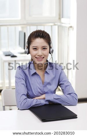 Businesswoman with headset reading portfolio