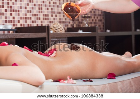cacao therapy applied to young woman in a spa - stock photo
