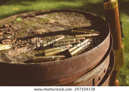 44 Caliber Bullets and Winchester Rifle. Winchester Centennial '66 Rifle and .30 (thirty-thirty) WCF ammunition on an old barrel in a rustic rural yard. Edited with a vintage filter. - stock photo