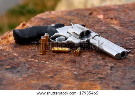44 caliber hand gun laying on the rad stone with cartridges