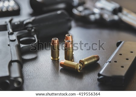 .45 Caliber hollow point bullets near handgun and magazine on leather furniture - stock photo