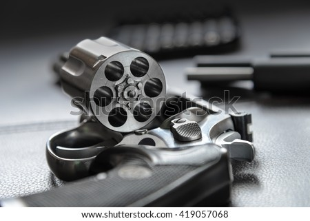 .357 Caliber Revolver Pistol, Revolver open ready to put bullets on leather furniture - stock photo