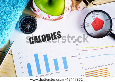 """Calories"" black text on paper with magnifying glass on red spider bar on wooden table with compass, pen, towel, green apple with measurement tape, and whistles - fitness, diet and healthy concept - stock photo"