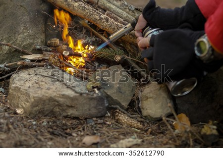 Campfire in winter forest, focus on center of bonfire - stock photo