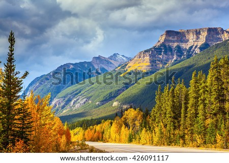 Canada, Alberta, Rocky Mountains. Highway in Banff National Park. Mountains and colorful autumn forest illuminated by the sunset