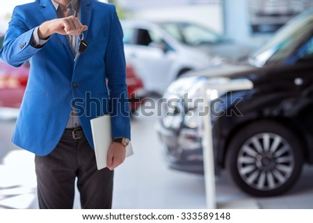car agent  in car dealership saloon holding car key in front of him - stock photo