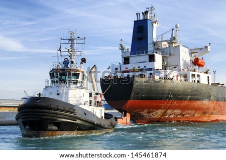 Cargo Ship and Tugboat  - stock photo