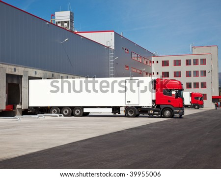 cargo trucks at an entrance of a warehouse
