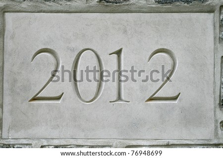 2012 carved on a gray stone block set in concrete