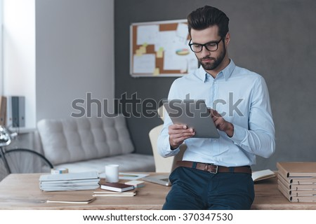Casual business day. Handsome young man wearing glasses and working with touchpad while leaning to the table in office  - stock photo