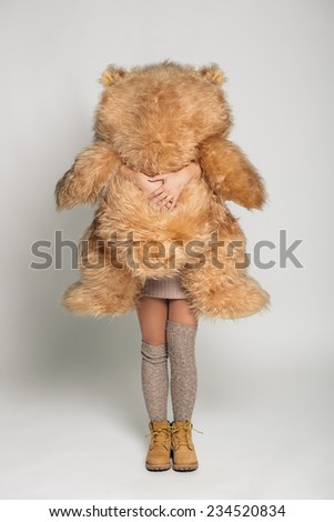 Casual smiling young woman in winter clothing holding big soft teddy bear on white background - stock photo
