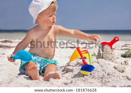 Caucasian baby (boy) in the hat is sitting at the beach. Cute child is playing with toys on the sand in summer day. Summer vacation concept. Outdoor.   - stock photo