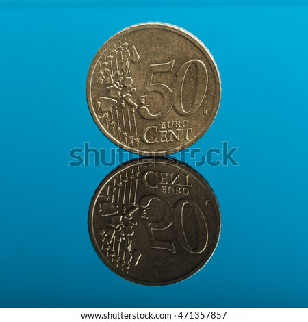 50 cents, Euro money coin on blue colored background with reflection on mirror surface, studio shot.
