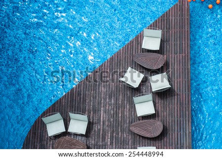 chair relax on in holiday swimming pool with clear blue water /  Empty sunbeds by the resort pool - stock photo